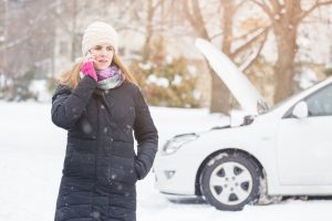 Female standing next to broken car and talking on mobile phone.